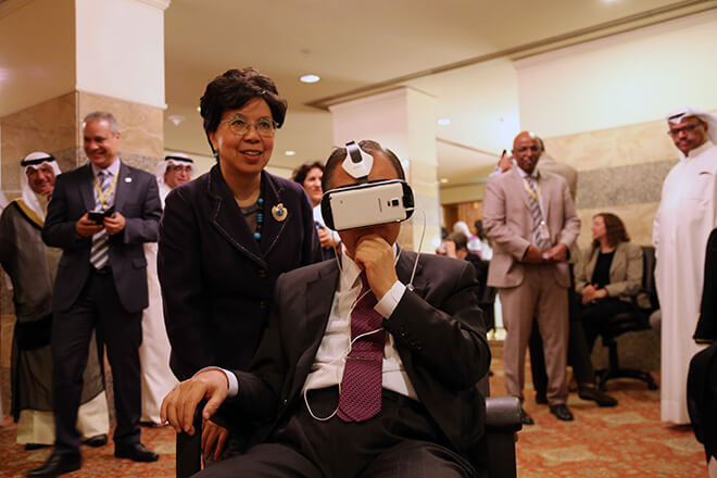 UN Secretary-General Ban Ki-moon sitting in a chair with a VR headset on, watching Clouds over Sidra, Executive Director, WHO Margaret Chan is standing by his side and they are both surrounded by Kuwaiti dignitaries.